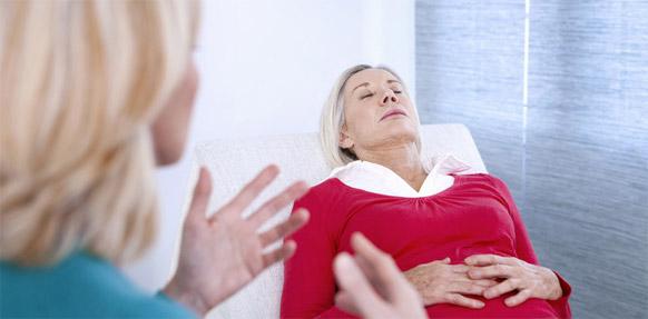 Frau liegt mit geschlossenen Augen auf Behandlungsbank. Zweite Frau steht gestikulierend daneben.